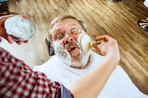 Emotionaler älterer mann, der friseur im friseurladen besucht