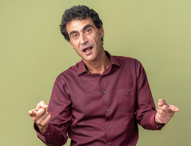 Emotionaler älterer mann in violettem hemd, der glücklich und aufgeregt in die kamera schaut und mit zeigefingern auf die kamera zeigt, die über grün steht