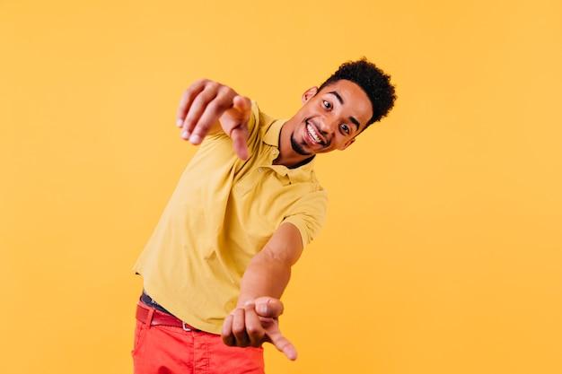 Emotionaler afrikanischer kerl, der mit lächeln schaut. froh, gut gekleideter schwarzer junge, der glück ausdrückt.