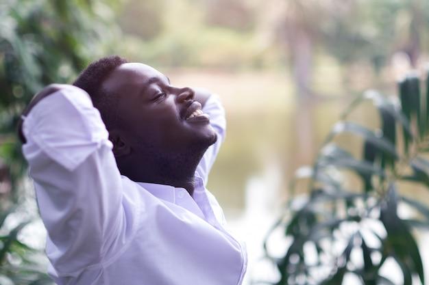 Emotionaler afrikanischer mann, der im wind lacht