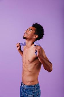 Emotionaler afrikanischer mann, der ohne t-shirt aufwirft. hübscher kerl, der steht und aufschaut.