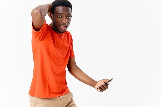 Emotionaler amerikaner mit einem telefon in den händen der technologie