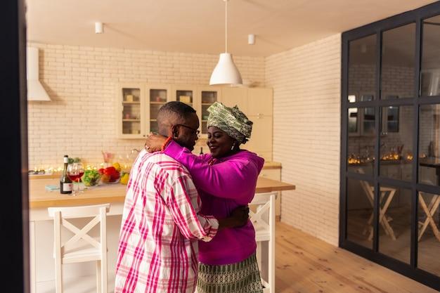 Emotionaler ausdruck. angenehmes gut aussehendes paar, das zusammen in der küche steht, während es einen tanz durchführt