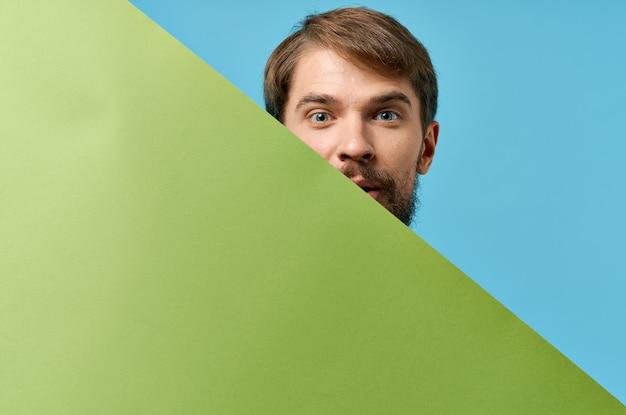 Emotionaler bärtiger mann, der hinter dem blauen hintergrund des grünen fahnenstudios herausschaut. hochwertiges foto