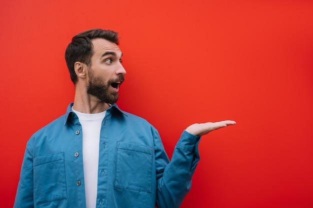 Emotionaler bärtiger mann, der mit hand zeigt, lokalisiert auf rotem hintergrund. kopierfläche, werbekonzept