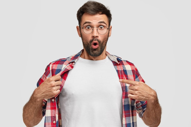 Emotionaler bärtiger mann mit verblüfften ausdruckspunkten an seinem weißen t-shirt, zeigt leerzeichen für ihr design, reagiert auf hohen preis, isoliert über weißer wand. empörter junger männlicher junge