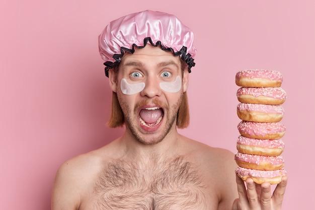 Emotionaler blauäugiger junger mann mit bob-frisur starrt in die kamera, ruft laut aus, hat weit geöffneten mund hält haufen von donuts