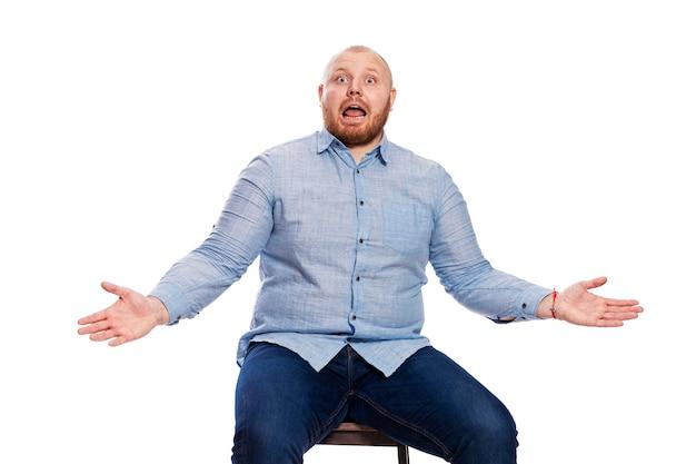 Emotionaler fetter roter mann mit einem bart in einem blauen hemd und in den jeans. das öffnen seines mundes zuckt die achseln und schaut