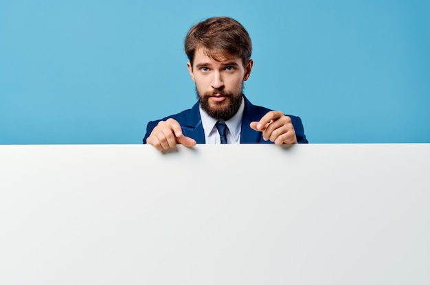 Emotionaler geschäftsmann, der aus hinter beschnittener blauer ansicht des banners herausschaut
