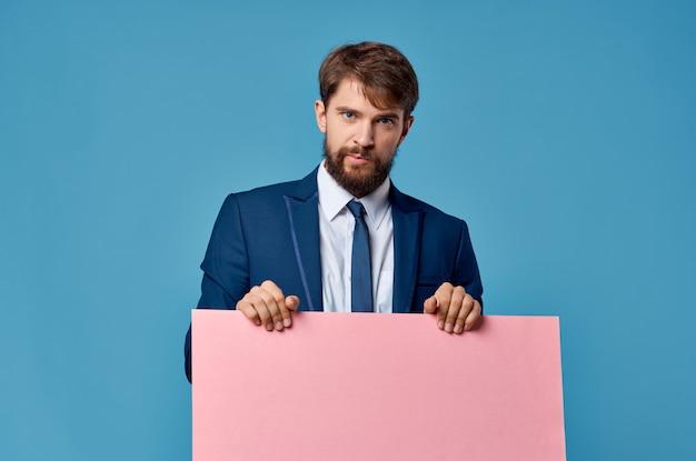 Emotionaler geschäftsmann im anzug rosa banner modellpräsentation blauen hintergrund
