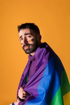 Emotionaler homosexueller mann eingewickelt in der lgbt-regenbogenflagge