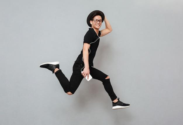 Emotionaler junger asiatischer mann, der isoliert springt