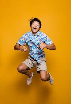Emotionaler junger asiatischer mann, der isoliert über gelben raum springt und daumen hoch zeigt.