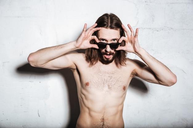 Emotionaler junger bärtiger hipster-mann mit sonnenbrille, der isoliert über der wand steht und nach vorne schaut