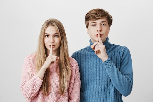 Emotionaler junger europäischer mann und frau mit blonden haaren gekleidet in rosa und blauen pullovern, die finger an den lippen halten