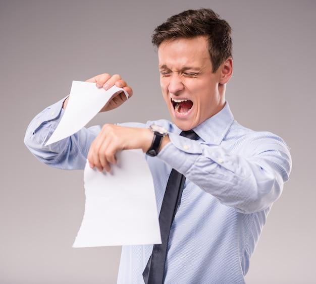 Emotionaler junger geschäftsmann, der papier zerreißt.