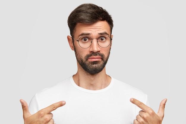 Emotionaler junger hübscher mann mit dickem dunklem bart, zeigt auf verwirrtes leeres t-shirt mit verwirrung