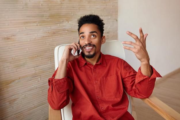 Emotionaler junger kurzhaariger bärtiger kerl mit dunkler haut, der anruft und froh lächelt, während er auf innenraum in gemütlichem stuhl mit erhabener hand sitzt