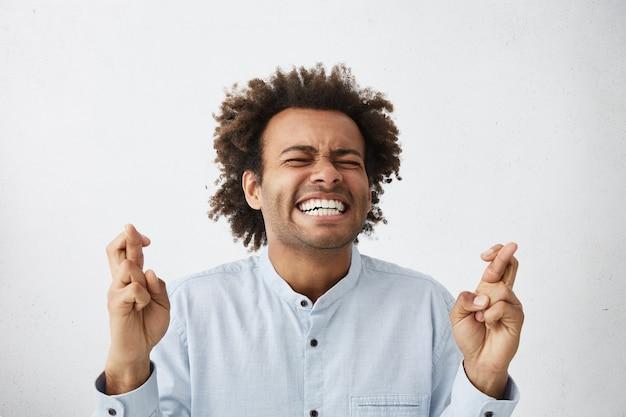 Emotionaler junger männlicher bewerber, der die augen fest schließt und die finger kreuzt