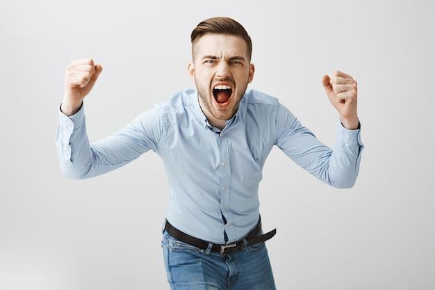 Emotionaler junger mann ballt fäuste und schreit aggressiv, sportspiel beobachtend