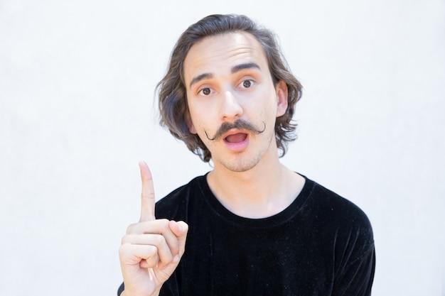 Emotionaler junger mann mit dem schnurrbart oben zeigend mit dem finger