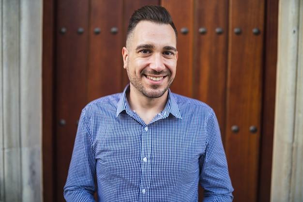 Emotionaler junger mann mit einem blauen hemd, das am tor mit einem leichten lächeln auf seinem gesicht steht