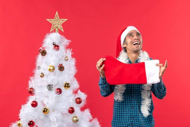 Emotionaler junger mann mit weihnachtsmannhut in einem blauen gestreiften hemd und halten der weihnachtssocke, die oben schaut