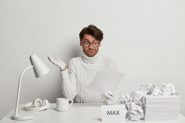 Emotionaler junger mann schaut mit verwirrtem ausdruck auf papierdokumente