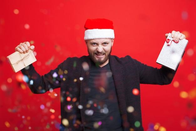 Emotionaler kaukasischer mann mit bart und weihnachtsmütze hält zwei geschenke an einer roten wand mit konfetti gesturig wut