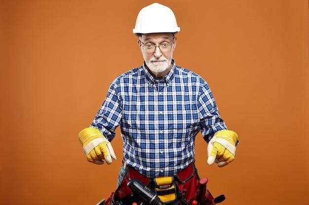 Emotionaler lustiger älterer älterer hausbauer, der schutzhelm, sicherheitshandschuhe und tasche mit instrumenten um seine taille trägt, die überraschten gesichtsausdruck schockiert und vorderfinger nach unten zeigt