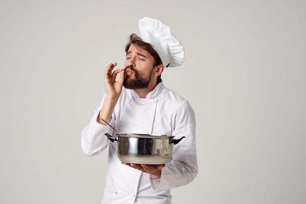 Emotionaler männlicher koch mit einem topf in seinen händen, der die restaurantindustrie kocht. foto in hoher qualität