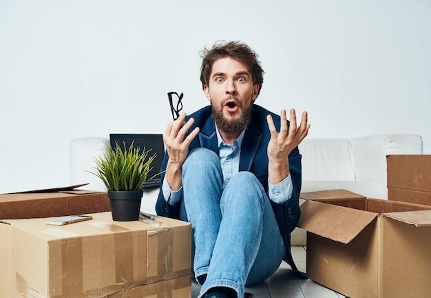 Emotionaler männlicher manager, der lebensstilkästen im büro auspackt