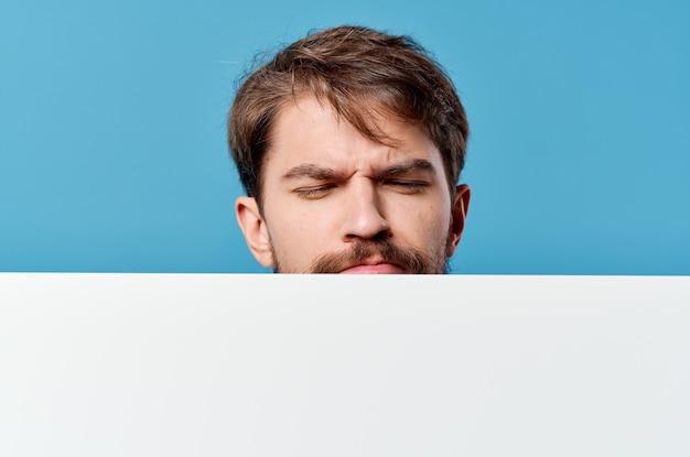 Emotionaler mann, der den blauen hintergrund des bannerwerbekopierraums hält