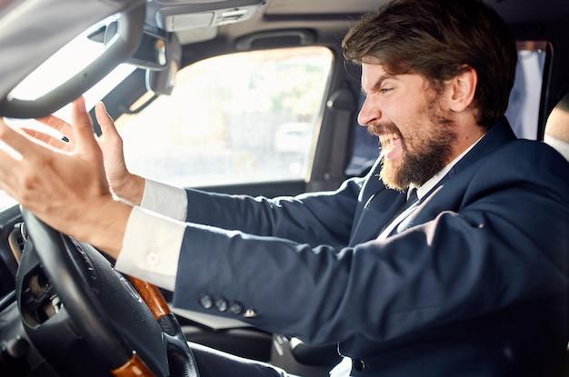 Emotionaler mann, der ein auto fährt, das mit seinen händen straßenbahn gestikuliert