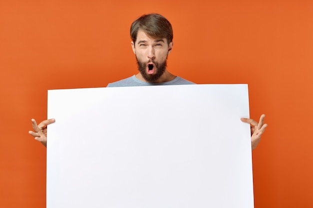 Emotionaler mann, der einen orangefarbenen hintergrund des mockup-plakats hält