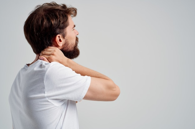Emotionaler mann, der hals-arthritis-gesundheitsprobleme hält, isolierter hintergrund. foto in hoher qualität