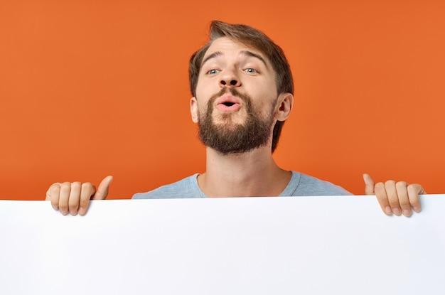 Emotionaler mann, der hinter einem plakat auf einem kopierraummodell des orangefarbenen hintergrunds herausschaut.