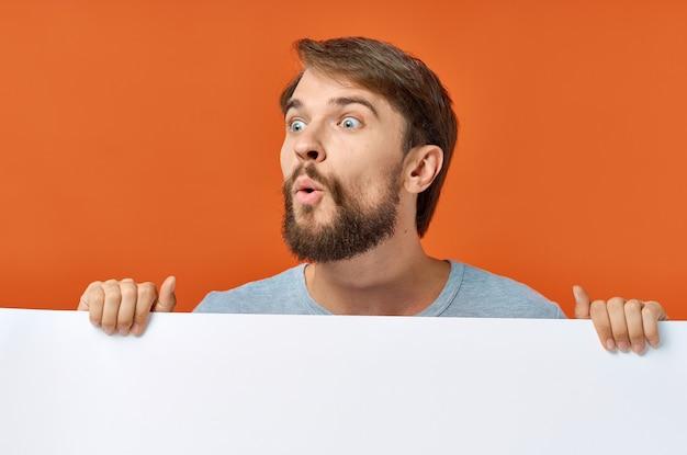 Emotionaler mann, der hinter einem plakat auf einem orangefarbenen hintergrund hervorschaut