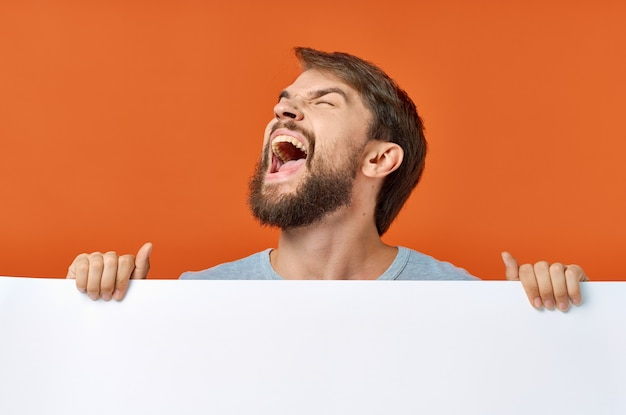 Emotionaler mann, der hinter einem plakat auf einem orangefarbenen kopierraummodell hervorschaut.