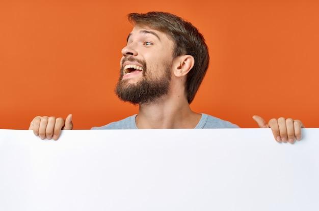 Emotionaler mann, der hinter einem plakat auf einem orangefarbenen modell hervorschaut