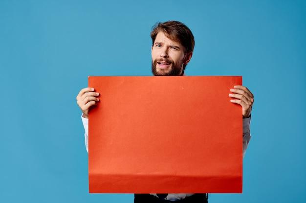 Emotionaler mann, der rote fahnenkommunikationswerbung lokalisierte blaue wand hält.