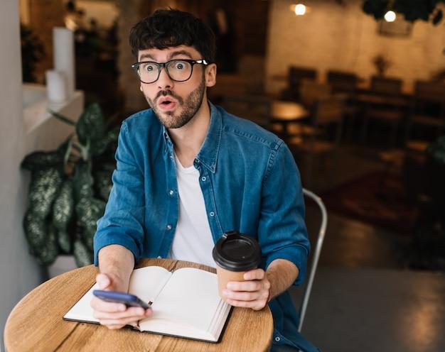 Emotionaler mann, der tasse kaffee und smartphone im café hält