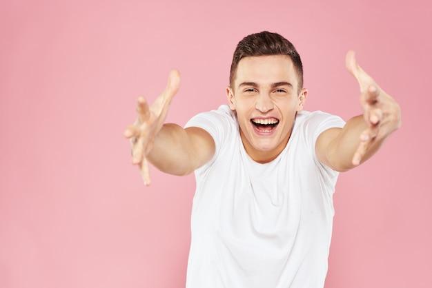 Emotionaler mann gestikuliert mit seinen händen weißes t-shirt rosa isoliert.