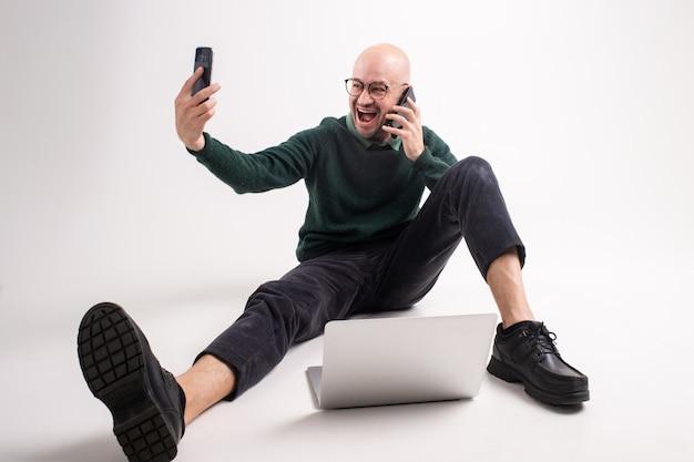 Emotionaler mann hält ein telefon, tablet und laptop, kommuniziert und arbeitet.