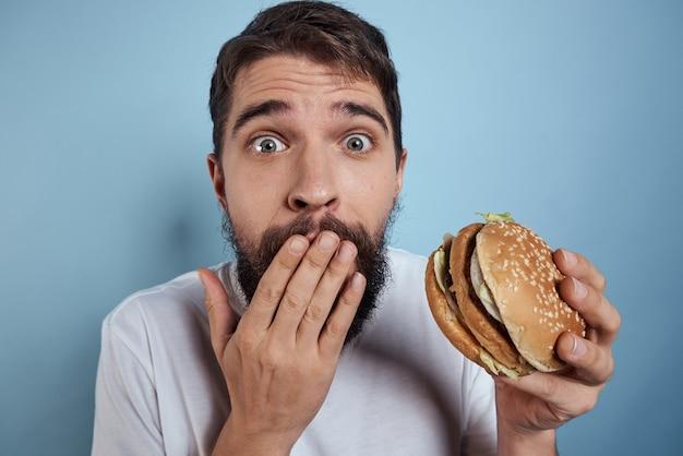 Emotionaler mann hamburger fast-food-diät-lebensmittel nahaufnahme blauen hintergrund. hochwertiges foto