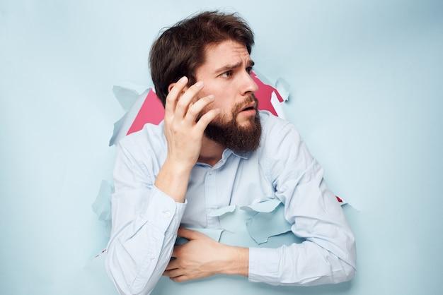 Emotionaler mann im blauen hemd bricht durch wandgefühle beschnittenes ansichtsbüro.