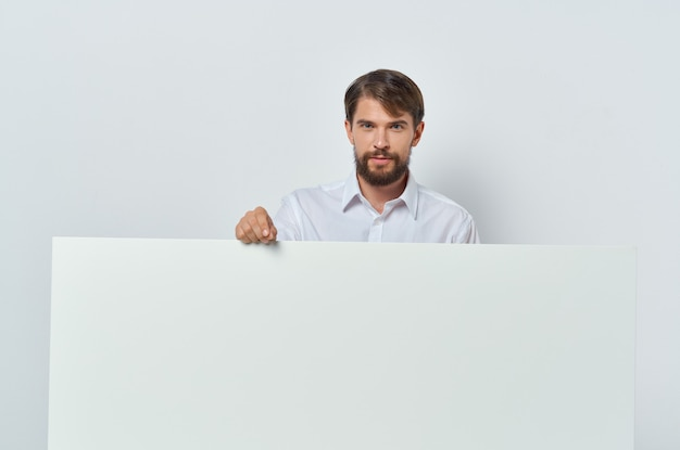 Emotionaler mann im hemd gestikuliert mit seinen händen weiße geschäftswerbung.