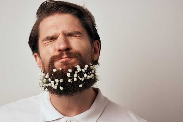 Emotionaler mann im weißen hemdbart, der blumen nahaufnahme verziert. hochwertiges foto