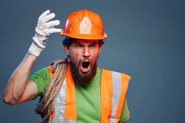 Emotionaler mann in der arbeitsuniform sicherheit professioneller blauer hintergrund.