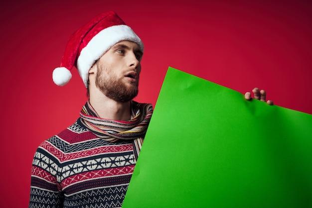 Emotionaler mann in der kleidung des neuen jahres, die kopienraum-roten hintergrund annonciert